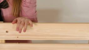 Primer de la mano de una niña en un banco de madera en un cuarto con una pared blanca almacen de video