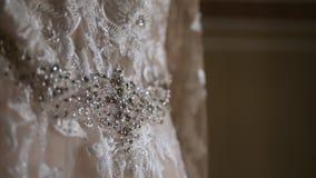 Primer de la marfil colgante del vestido de boda bordada con los diamantes artificiales metrajes
