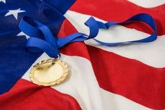 Primer de la medalla de oro en bandera americana Foto de archivo libre de regalías