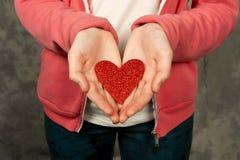 Primer de la muchacha adolescente que lleva a cabo el corazón rojo Imagenes de archivo
