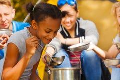 Primer de la muchacha africana que cocina la sopa en el sitio para acampar Fotos de archivo libres de regalías