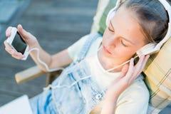 Primer de la muchacha bastante adolescente en auriculares que escucha el usi de la música Fotos de archivo libres de regalías