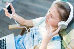 Primer de la muchacha bastante adolescente en auriculares que escucha el usi de la música Imagen de archivo