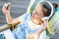 Primer de la muchacha bastante adolescente en auriculares que escucha el usi de la música Foto de archivo libre de regalías
