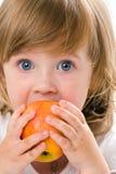 Primer de la muchacha bonita que come una manzana, aislado Foto de archivo