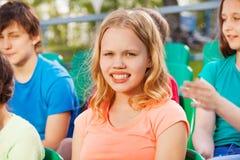 Primer de la muchacha del adolescente que se sienta en la tribuna Fotografía de archivo