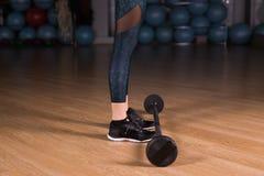 Primer de la muchacha del ajuste que ejercita los músculos del edificio Aptitud y levantamiento de pesas Imagen de archivo