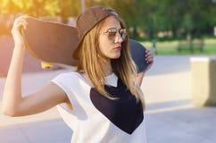 Primer de la muchacha del patinador que sostiene el monopatín detrás de su cabeza Fotografía de archivo