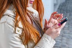 Primer de la muchacha del redhair que manda un SMS en el teléfono móvil Fotos de archivo