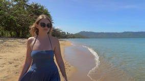 Primer de la muchacha europea joven en gafas de sol y vestido azul que camina en la playa arenosa contra la perspectiva de almacen de metraje de vídeo