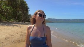 Primer de la muchacha europea joven en gafas de sol y vestido azul que camina en la playa arenosa contra la perspectiva de metrajes