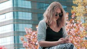 Primer de la muchacha europea joven hermosa en las gafas de sol que se sientan en la calle y que usan smartphone con los rascacie metrajes