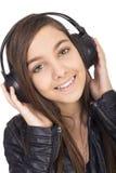 Primer de la muchacha feliz con música que escucha de los auriculares Imagen de archivo libre de regalías