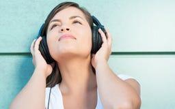 Primer de la muchacha hermosa joven que disfruta de música en los auriculares Imágenes de archivo libres de regalías