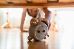 Primer de la muchacha hermosa que alcanza para el despertador debajo de la cama Imagen de archivo libre de regalías