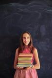 Primer de la muchacha hermosa que se coloca con los libros en su agai de las manos Imágenes de archivo libres de regalías