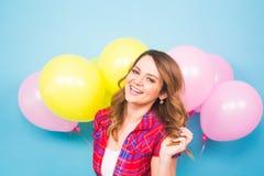 Primer de la muchacha morena linda que se coloca en un estudio, sonriendo extensamente y jugando con los globos amarillos y rosad Imagen de archivo