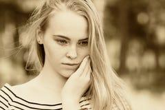 Primer de la muchacha pensativa en una mirada rayada del vestido Fotos de archivo