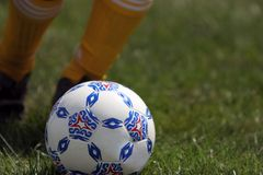 Primer de la muchacha que golpea el balón de fútbol con el pie imagen de archivo libre de regalías