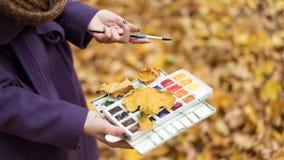 Primer de la muchacha que sostiene las pinturas y el cepillo en manos en el parque del otoño imagenes de archivo