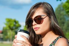 Primer de la muchacha que sostiene y que mira el café para llevar Fotos de archivo