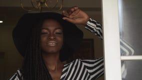 Primer de la mujer afroamericana de moda elegante en sombrero negro y el vestido rayado que presentan en sus apartamentos de lujo almacen de metraje de vídeo