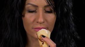 Primer de la mujer atractiva que lame el cono de la galleta del helado de nata con el chocolate que remata el alto bocado calóric metrajes