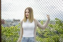 Primer de la mujer bastante joven que coloca la cerca cercana de la alambrada Fotografía de archivo