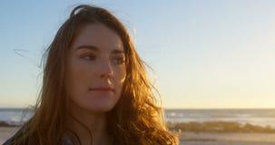 Primer de la mujer bonita pensativa en la playa durante la puesta del sol 4k almacen de video