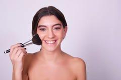 Primer de la mujer caucásica joven que aplica maquillaje Imagenes de archivo
