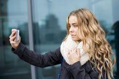 Primer de la mujer caucásica joven rubia feliz hermosa que toma un selfie en smartphone al aire libre en parque en otoño Fotografía de archivo libre de regalías