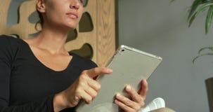 Primer de la mujer caucásica que usa la tableta digital en pasillo en el hospital 4k almacen de video