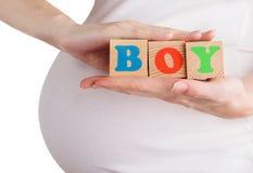 Primer de la mujer embarazada que lleva a cabo bloques de madera con la muestra del muchacho aislada en blanco Foto de archivo