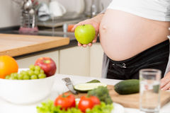 Primer de la mujer embarazada que presenta con la manzana verde en cocina Fotos de archivo