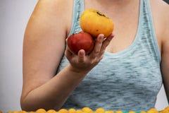 Primer de la mujer en el top sin mangas que sostiene dos tomates de la herencia en su mano en el mercado de los granjeros - irrec fotos de archivo