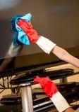 Primer de la mujer en los guantes de goma que limpian la pantalla de la TV con el trapo Imagen de archivo
