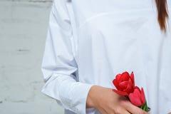 Primer de la mujer en uniforme con las flores rojas en sus manos imagenes de archivo