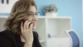 Primer de la mujer hermosa usando Smartphone Señora del negocio en vestido del desgaste formal que habla discutiendo problemas en almacen de video