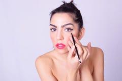 Primer de la mujer hispánica joven que aplica maquillaje Fotos de archivo libres de regalías