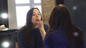 Primer de la mujer joven bonita en la situaci?n azul marino del puente delante del espejo grande y la pintura de sus labios media metrajes