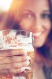 Primer de la mujer joven con un vidrio de cerveza fotografía de archivo libre de regalías