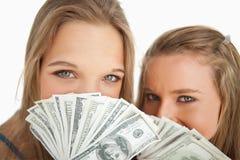 Primer de la mujer joven dos detrás de dólares Imagenes de archivo