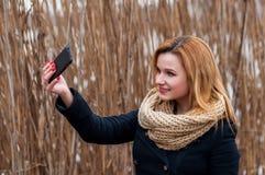 Primer de la mujer joven hermosa que toma una foto del selfie con el teléfono elegante al aire libre Imagen de archivo libre de regalías
