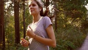 Primer de la mujer joven que activa y que escucha la música en sus auriculares almacen de video