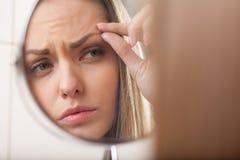 Primer de la mujer joven que mira en el espejo foto de archivo