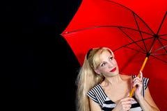 Primer de la mujer joven que sostiene el paraguas rojo imagenes de archivo