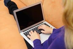 Primer de la mujer joven que usa el ordenador portátil en el sofá Foto de archivo
