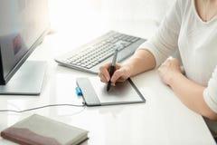 Primer de la mujer joven que usa la tableta gráfica en la oficina Fotografía de archivo