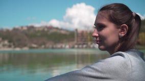 Primer de la mujer joven, sentándose por el lago en un día de primavera, relajándose en naturaleza almacen de metraje de vídeo