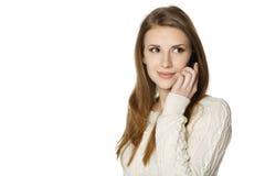 Primer de la mujer joven sonriente que habla en el teléfono celular Fotografía de archivo libre de regalías